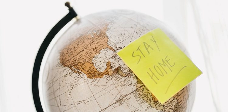 Stay home note on a globe